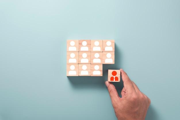 El desarrollo humano y el concepto de pensamiento diferente, la mano que sostiene el icono del administrador rojo de la pantalla impresa del bloque del cubo de madera se mueve fuera de los iconos humanos blancos.