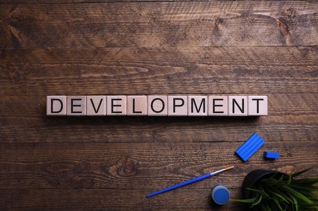 Desarrollo de palabras cubos de madera, bloques sobre el tema de la educación, el desarrollo y la formación en una mesa de madera. vista superior. lugar para el texto.