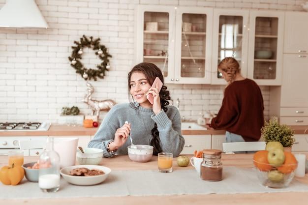 Desayunar ligero. linda chica de pelo oscuro participa en una conversación a través de un teléfono inteligente mientras está sentada en la cocina con estilo