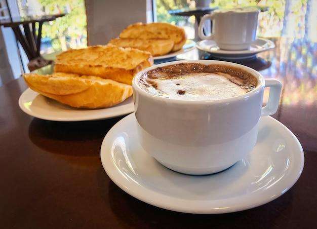 Desayune en el brasil con el pan francés tostado con mantequilla en la placa con capuccino en la tabla.