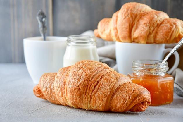 Desayune dos tazas de café con leche, dos cruasanes y mermelada de manzana en un frasco de vidrio.