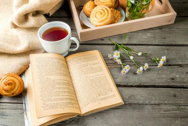 Desayuno acogedor en primavera o té de principios de otoño, bollos recién horneados y un ramo de margaritas de campo y un libro fascinante. copia espacio