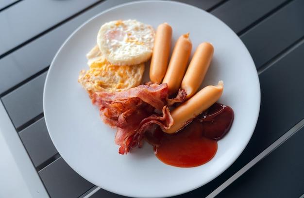 Desayuno americano casero en un plato blanco, tocino asado, salchichas, huevo frito y salsa de tomate en la mesa de madera.