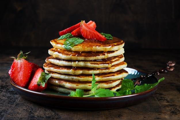 Desayuno americano clásico panqueque con miel y bayas. bodegón de exuberantes panqueques, miel y fresas.