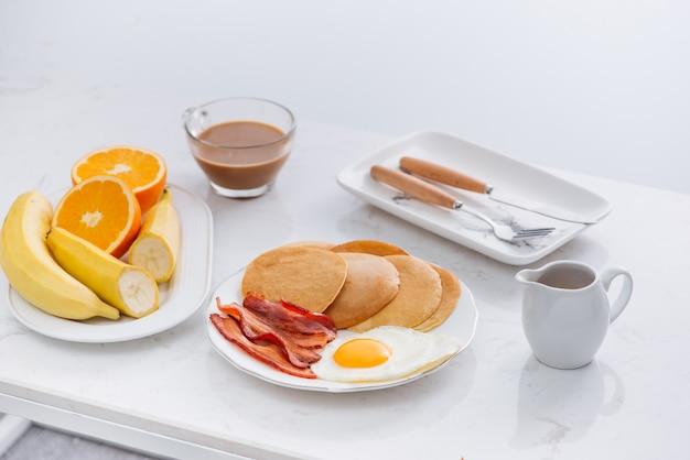 Desayuno americano completo saludable con huevos, tocino y panqueques