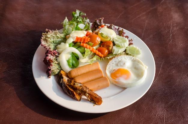 Desayuno americano, huevo frito, salchichas, mezcla de frutas y verduras en el plato