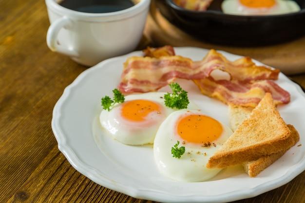 Desayuno americano con huevos fritos, tocino, tostadas, panqueques, café y jugo.