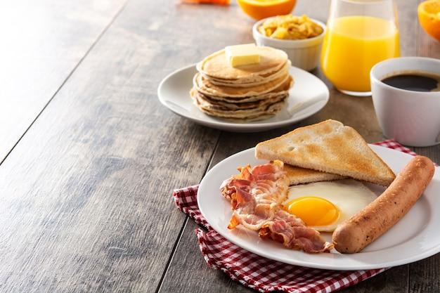 Desayuno americano tradicional con huevo frito, tostadas, tocino y salchichas en mesa de madera