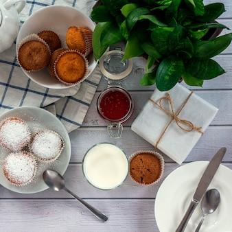 Desayuno amplio y luminoso con magdalenas, mermelada de bayas y leche en vaso.