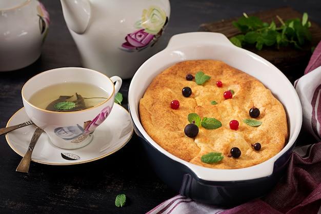 Desayuno. apetitosa cazuela de requesón en la mesa oscura.