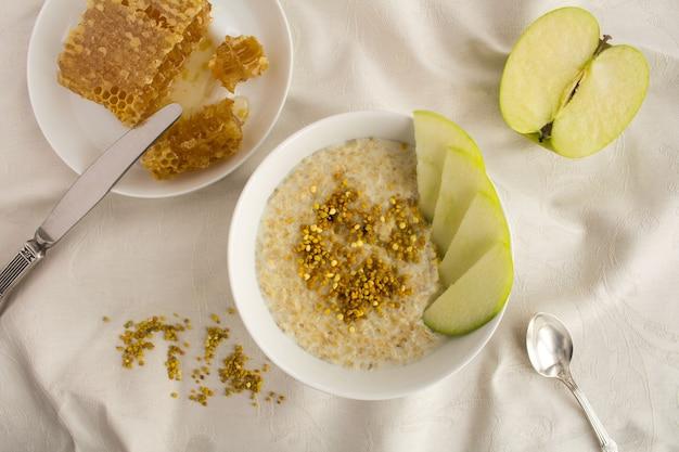 Desayuno: avena con polen de abeja, miel y manzana en el recipiente blanco sobre el fondo textil.vista superior.