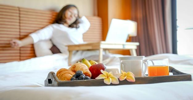 Desayuno en una bandeja en la cama en la habitación del hotel de lujo frente a una mujer asiática que viaja con una computadora portátil