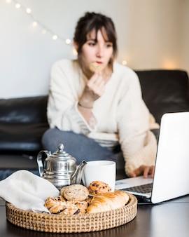 Desayuno en bandeja frente a mujer usando laptop