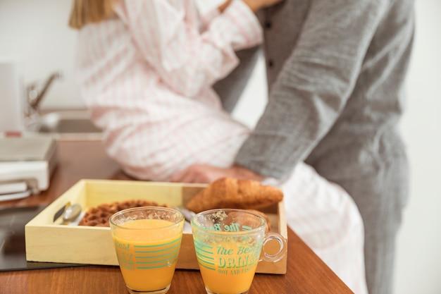 Desayuno en bandeja de madera con zumo en cocina.