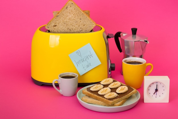 Desayuno brillante y divertido. tostadora amarilla y una taza de café sobre un fondo rosa.