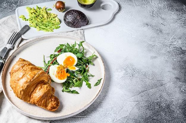 Desayuno, brunch con aguacate, rúcula, croissant y huevo. fondo gris vista superior. espacio para texto