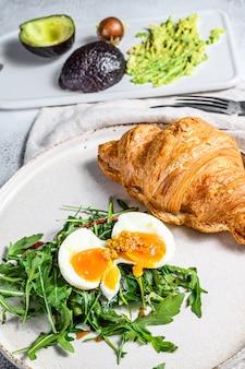 Desayuno, brunch con aguacate, rúcula, croissant y huevo. fondo gris vista superior