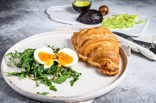 Desayuno, brunch con aguacate, rúcula, croissant y huevo. superficie gris. vista superior