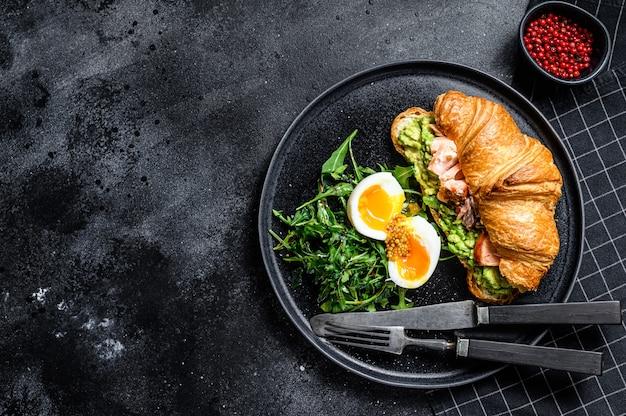Desayuno, brunch croissant con salmón ahumado caliente, aguacate. ensalada verde de jardín con rúcula y huevo. fondo negro. vista superior. espacio para texto
