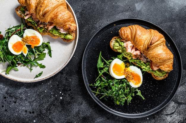 Desayuno, brunch croissant con salmón ahumado caliente, aguacate. ensalada verde de jardín con rúcula y huevo. superficie negra. vista superior