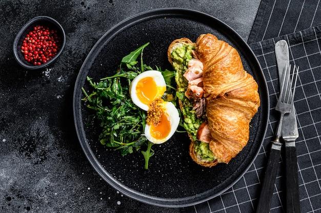 Desayuno, brunch croissant con salmón ahumado caliente, aguacate. ensalada verde de jardín con rúcula y huevo. vista superior