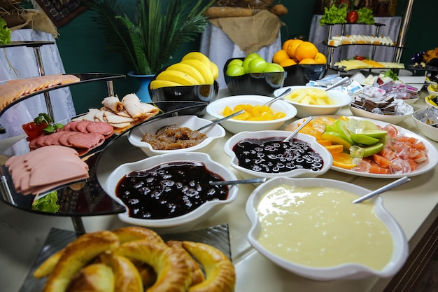 Desayuno buffet salchichas jamón frutas verduras mermeladas vista lateral