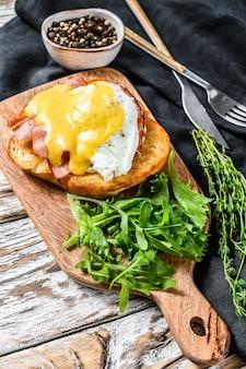 Desayuno burger con tocino, huevo benedict, salsa holandesa sobre pan brioche. adorne con ensalada de rúcula.