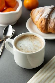 Desayuno café con croissant, cítricos franceses, pastelería, una taza de café o café con leche. la cafeína adicta.