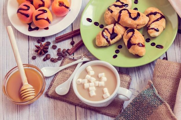 Desayuno de café, croissants, albaricoques, miel, canela y anís.
