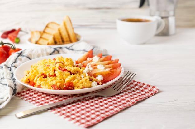 Desayuno con café, huevos revueltos con pimiento, tomate y queso, servido con tostadas.