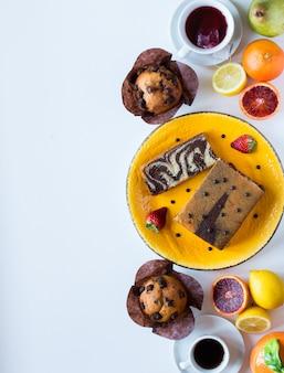 Desayuno con café y té con diferentes pasteles y frutas en una mesa de madera blanca.