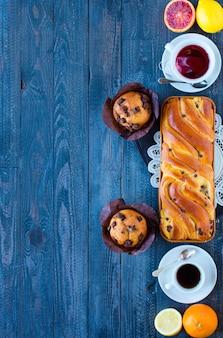 Desayuno con café y té con diferentes pasteles y frutas en una mesa de madera.
