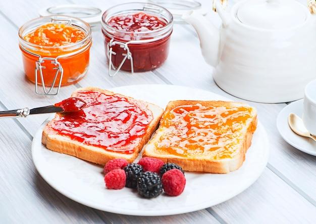 Desayuno de café, tostadas con mermelada de fresa y naranja junto a moras en un plato.