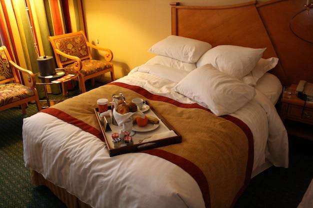 Desayuno en la cama, acogedora habitación de hotel.