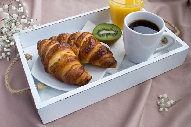 Desayuno en la cama en la bandeja de madera blanca.