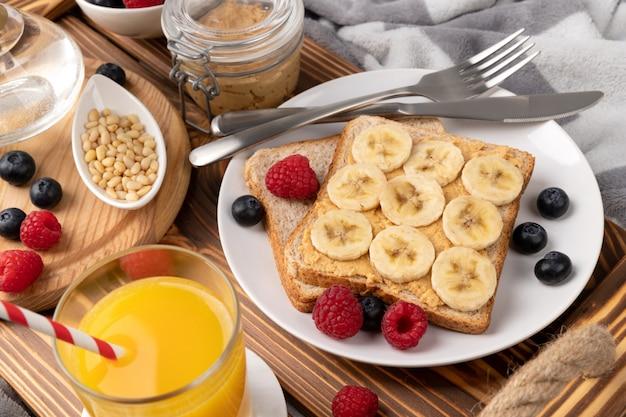 Desayuno en la cama. bandeja de madera con vaso de zumo de naranja y sandwich con frutas del bosque