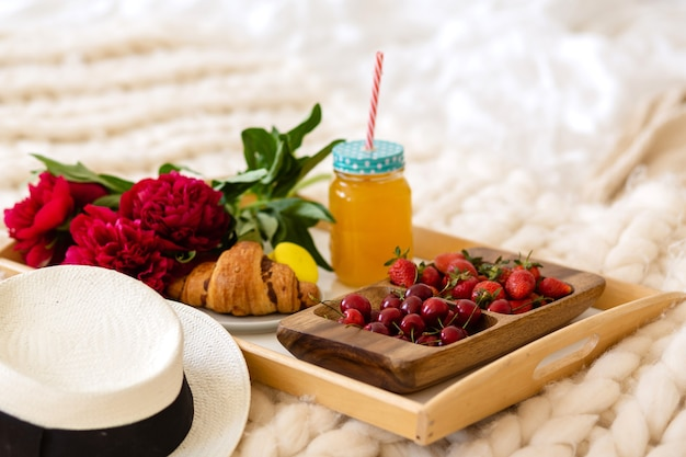 Desayuno en la cama con café, croissants, fresas y jugo.