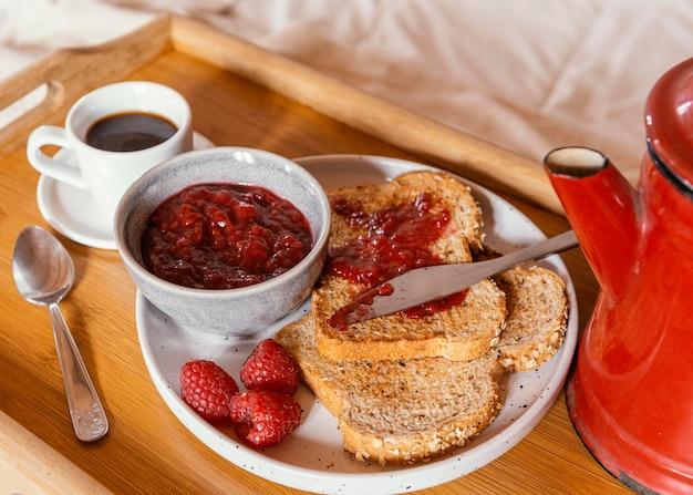 Desayuno en la cama con café y mermelada de ángulo alto.