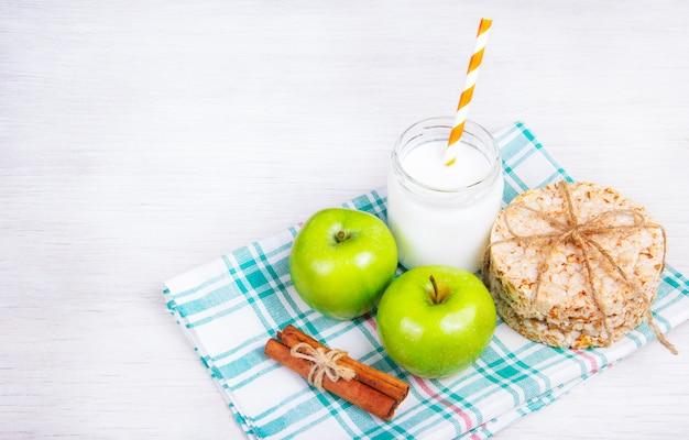 Desayuno campestre. pan de miel, manzanas verdes y yogurt con canela. copia espacio