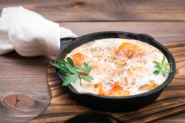 Desayuno casero de huevos fritos de shakshuka con tomates y hierbas en una sartén sobre una mesa de madera