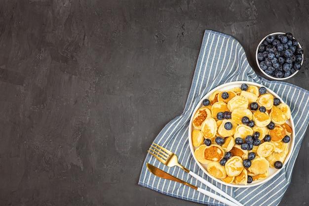 Desayuno casero de moda con pequeños panqueques y arándanos sobre fondo de hormigón gris. plano, vista superior, sobrecarga, maqueta, plantilla, espacio de copia. vista desde arriba