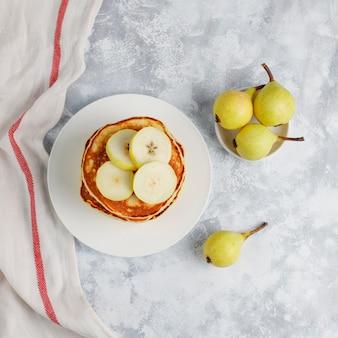 Desayuno casero: tortitas de estilo americano servidas con peras y miel con una taza de té en concreto. vista superior y copia