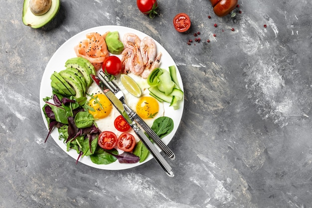 Desayuno cetogénico para la dieta cetogénica. desayuno de salmón, camarones cocidos, langostinos, huevos fritos, ensalada fresca, tomates, pepinos y aguacate. vista superior. concepto de dieta baja en carbohidratos. dieta alta en grasas.