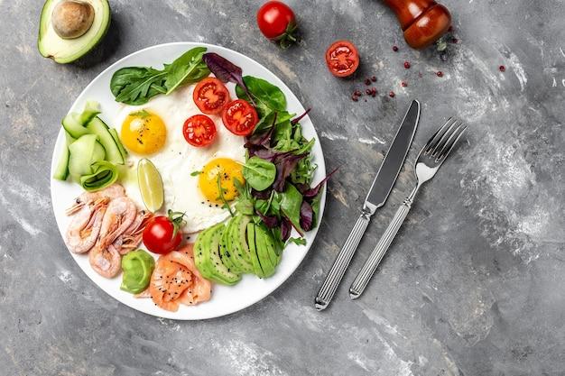 Desayuno cetogénico. salmón ceto bajo en carbohidratos, camarones cocidos, camarones, huevos fritos, ensalada fresca, tomates, pepinos y aguacate. vista superior. concepto de dieta baja en carbohidratos. dieta alta en grasas.