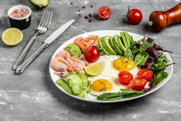 Desayuno cetogénico. salmón ceto bajo en carbohidratos, camarones cocidos, camarones, huevos fritos, ensalada fresca, tomates, pepinos y aguacate. vista superior.