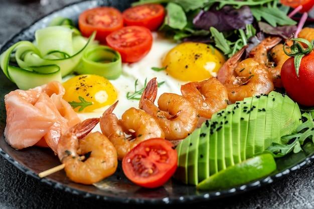 Desayuno cetogénico. salmón ceto bajo en carbohidratos, camarones a la parrilla, camarones, huevos fritos, ensalada fresca, tomates, pepinos y aguacate. dieta cetogénica. vista superior.