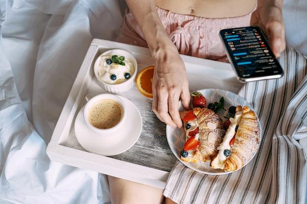 Desayuno conceptual en la cama, croissant con fresas y crema en una bandeja de madera clara con una taza de café