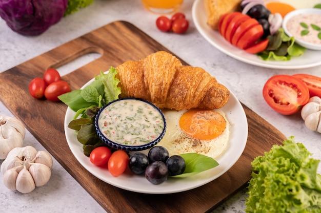 El desayuno consiste en croissant, huevo frito, aderezo para ensalada, uvas negras y tomates.