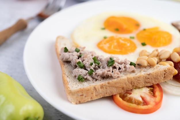 El desayuno consiste en huevos fritos, salchichas, carne de cerdo picada, pan, frijoles rojos y soja en un plato blanco.