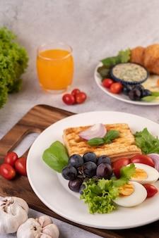 El desayuno consiste en pan, huevos duros, aderezo de ensalada de uva negra, tomates y cebollas en rodajas.